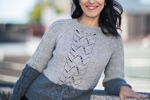Woman smiling at the camera, wearing a handknit sweater in 2 shades of gray.