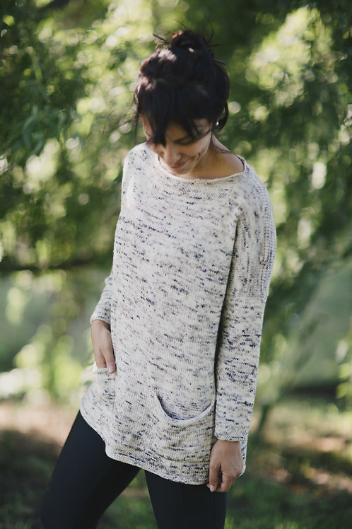 Woman looking down wearing light colored speckled sweater