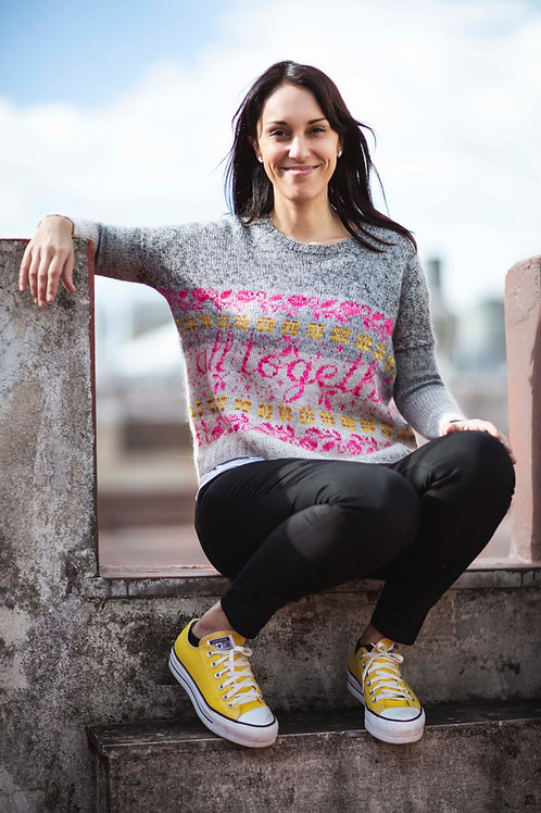 Woman sitting on a terrace, wearing a gray pullover with neon pink and yellow colorwork motifs.