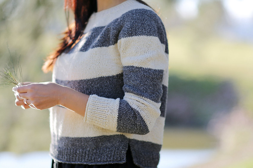 Cropped view of a woman wearing a striped white and gray cotton sweater. She's holding grass in her hands.
