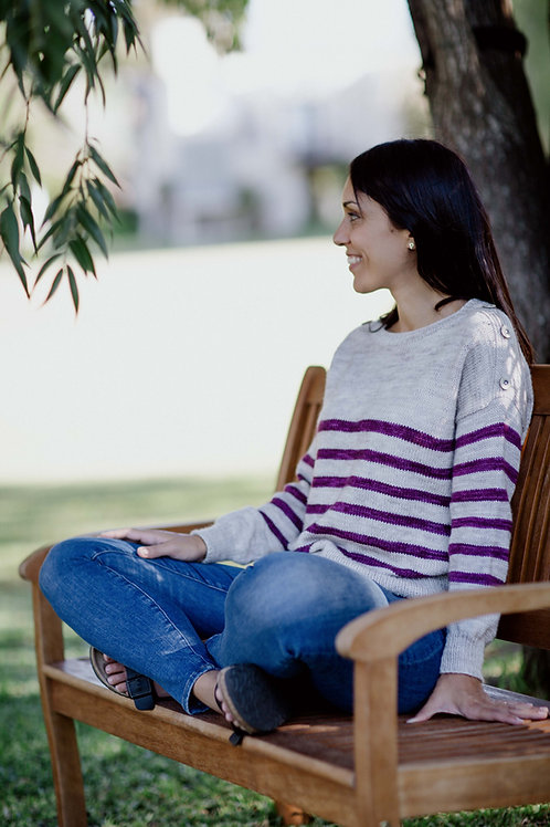 Woman sitting on a bench, looking at the horizon, wearing a striped pullover.