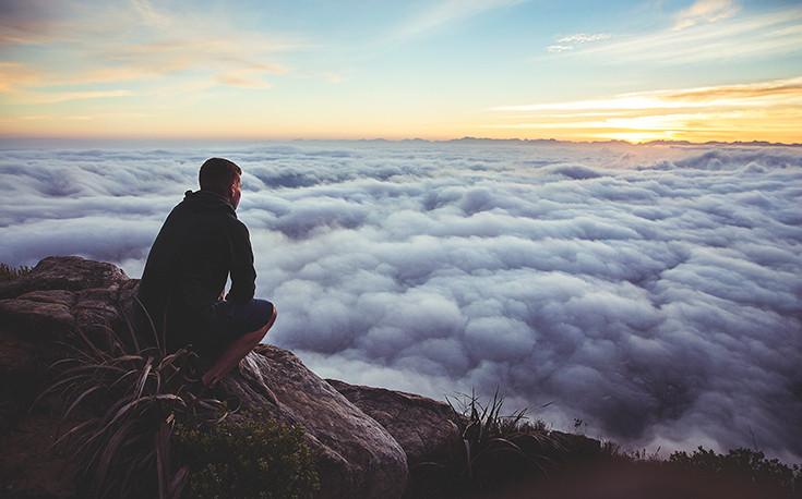 joven mirando el amanecer y las nubes