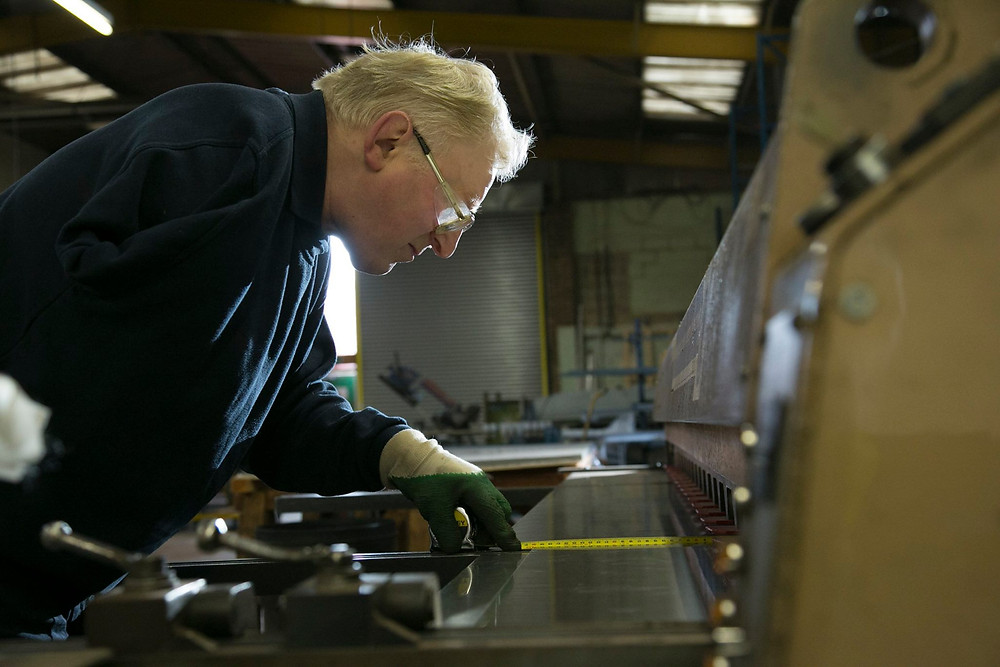 A person in workwear and protective goggles works in a manufacturing warehouse