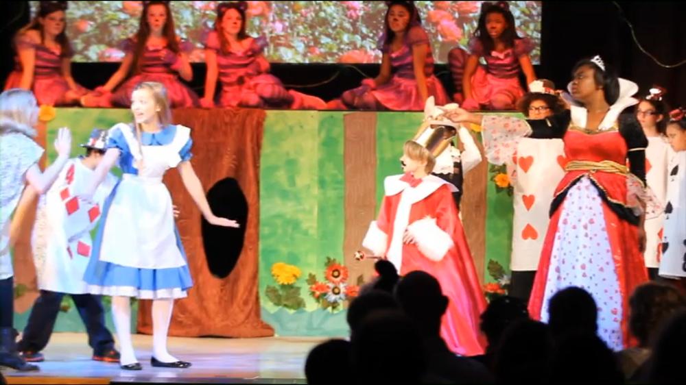 Une capture d'écran de mauvaise qualité de la comédie musicale Alice in Wonderland Jr interprétée par la Oliver Middle School en 2014