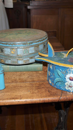 This picture shows different style of lunch boxes. The first two are tin and the third one is a wooden rosemaled tine (Norwegian lunchbox).
