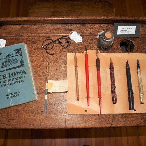 See the pens that were used in 1900. They had to be dipped in ink to be able to write. If you had to wear glasses, they might have looked like the ones in the picture. There is a slate pencil to use on a slate board and a book about the beginning and growth of Iowa.