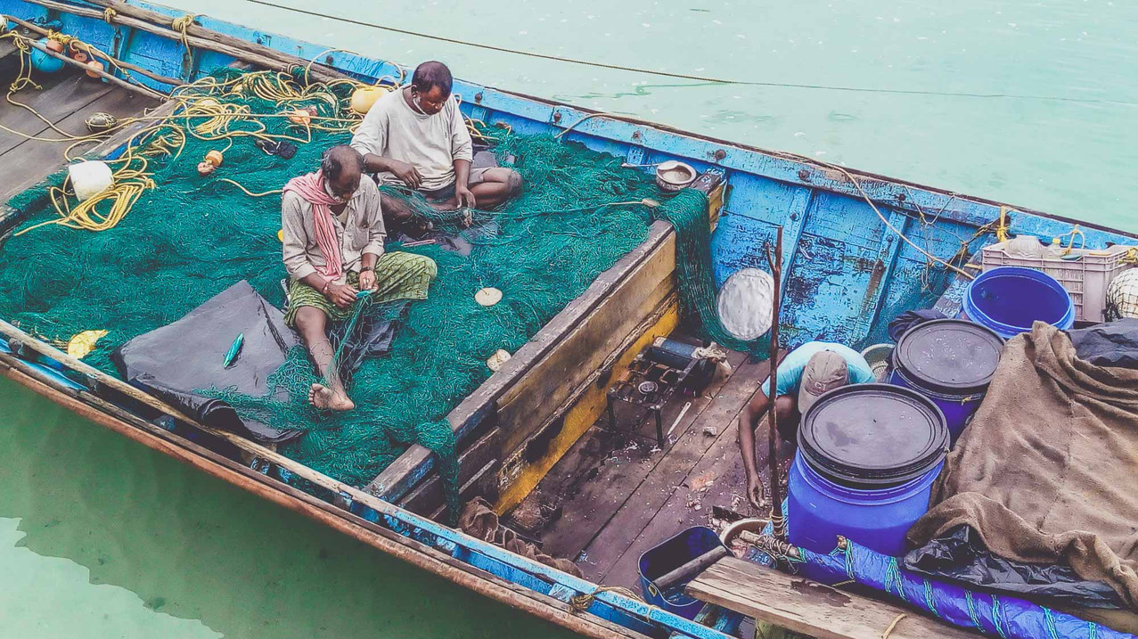 Fishermen mending the net, a part of their daily chore before fishing.