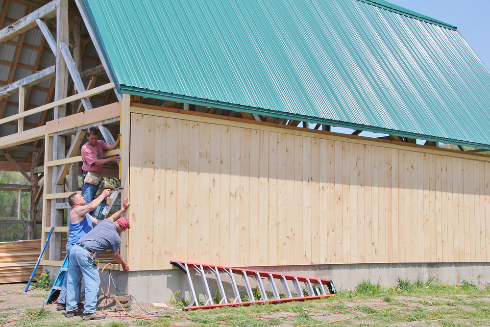 Workers install siding on the Finger Lakes Museum & Aquarium's Creekside Center.