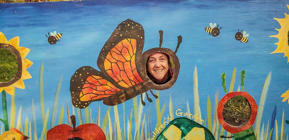 FLM&A Program Director Debbie behind a butterfly painting at Ithaca Children's Garden