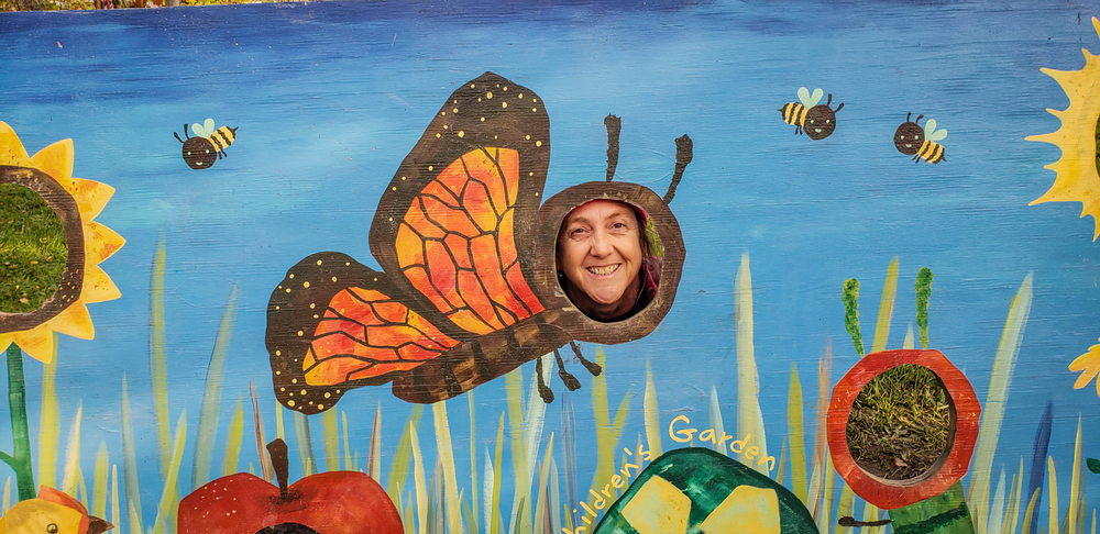 FLM&A Program Director Debbie behind a butterfly painting at Ithaca Children's Garden
