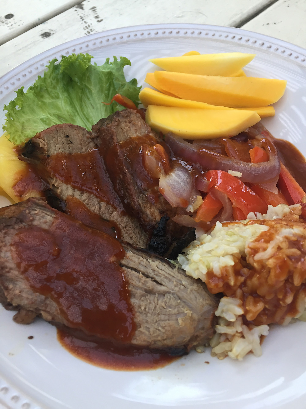 beef, rice, and fruit on a serving plate