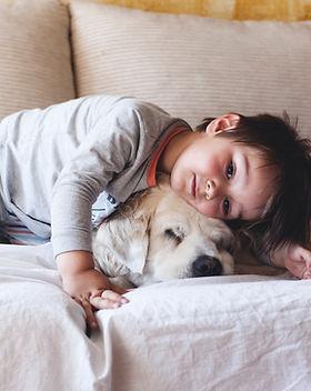 Boy Cuddling with his Dog