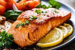 Fried salmon steak with potatoes and vegetables on wooden table.jpg