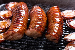 Polish traditional sausages fried on a c