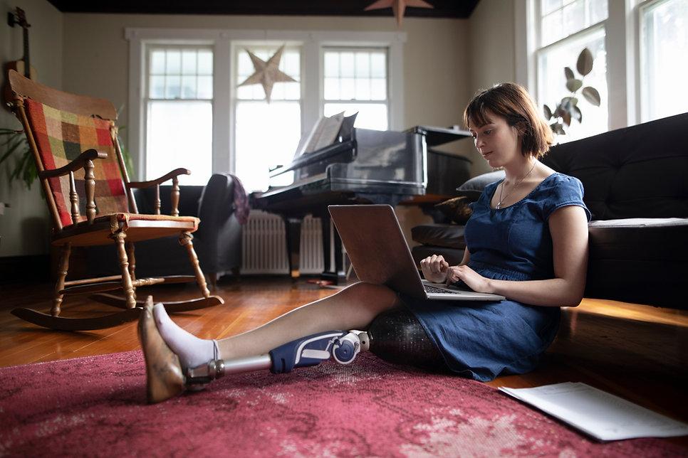 Frau mit dem Amputierten, der Laptop ver