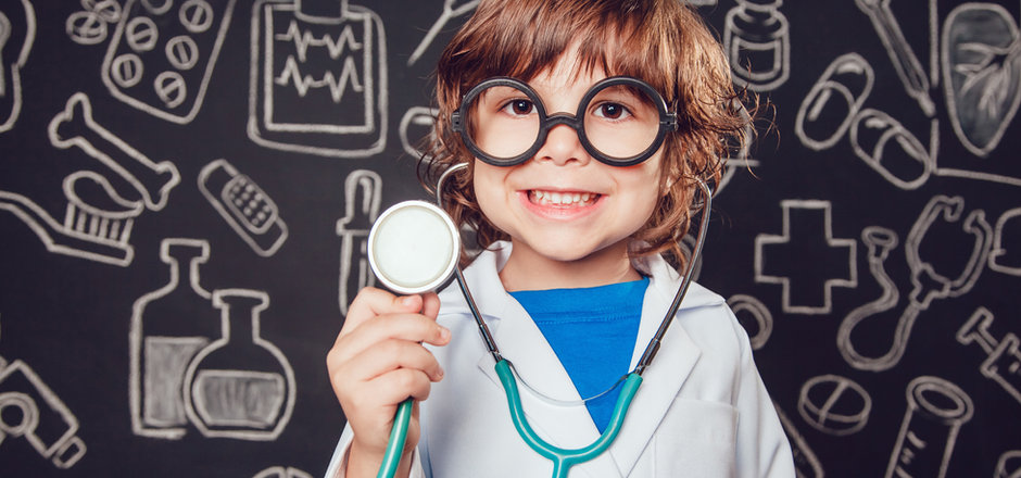 Happy little boy in doctor costume holdi