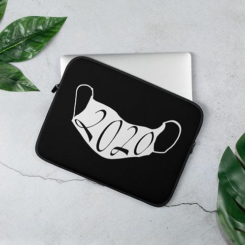 white 2020 mask on a black laptop sleeve