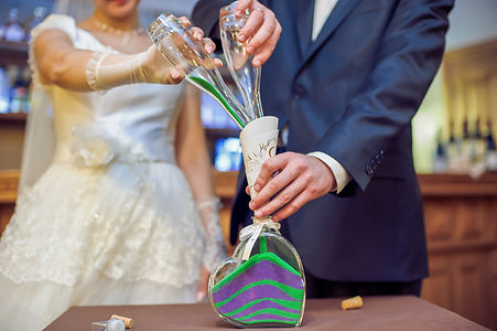 The bride and groom colorful sand is poured into the bottle.jpg