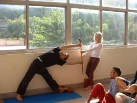 yoga stretch - man getting stretched by iyengar yoga teacher