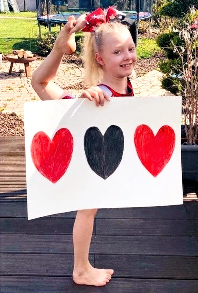 child with a heart sign in yoga shape