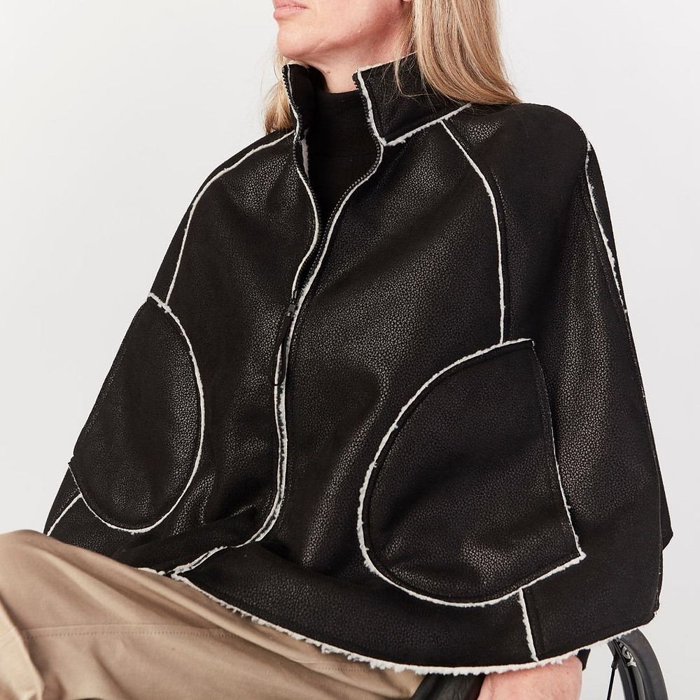 Wheelchair friendly winter cape worn by women sitting in wheelchair. Color: black with fur lining.
