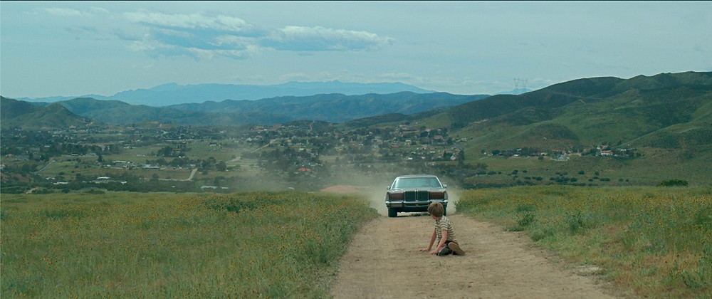 Still from the film A Strange Calm featuring a boy sitting on a dusty path and a car approaching behind him.