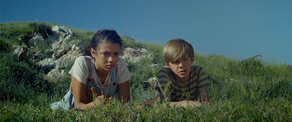Still from the film A Strange Calm featuring a young girl and boy on a cliff top.