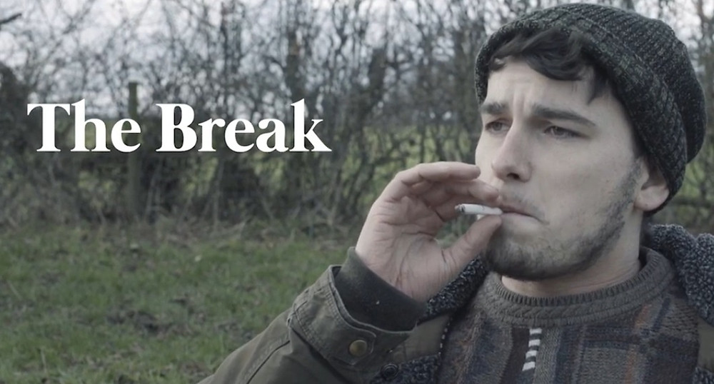 Still from short film The Break featuring a man in a field smoking a cigarette.
