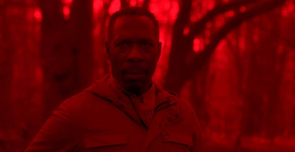 Gary Beadle in the woods with a strong red filter across the image.