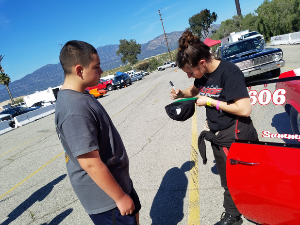 Hannah Maloof signing a fans hat