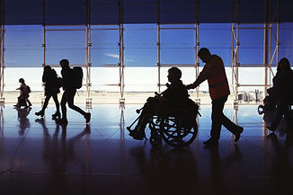 Silhouette of  man in wheelchair and peo