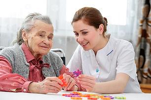 Elder care nurse playing jigsaw puzzle w