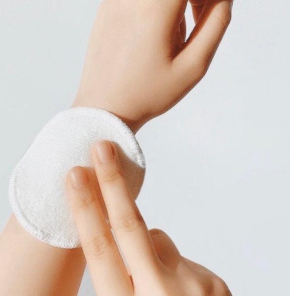 ID: a hand holding a Meiyu makeup wipe against a wrist