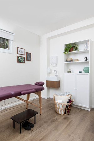 חדר טיפולים מרווח עם מיטת טיפולים, כיור ושולחן עבודה