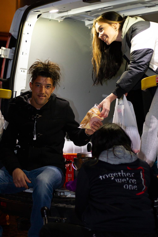 vrijwilliger geeft brood aan dakloze