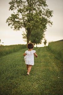 girl-standing-on-grass-field-facing-tree