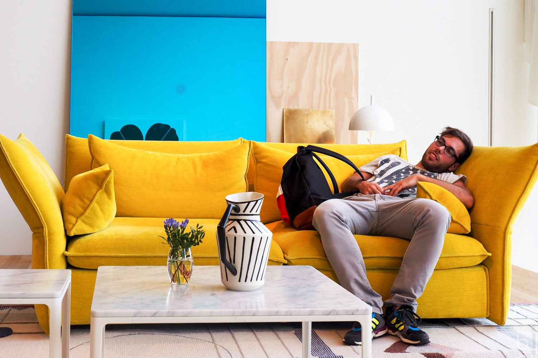 Mann auf gelbem Sofa