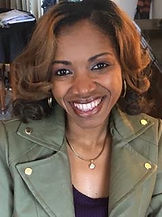 African-American woman with loose, honey brown curls smiling