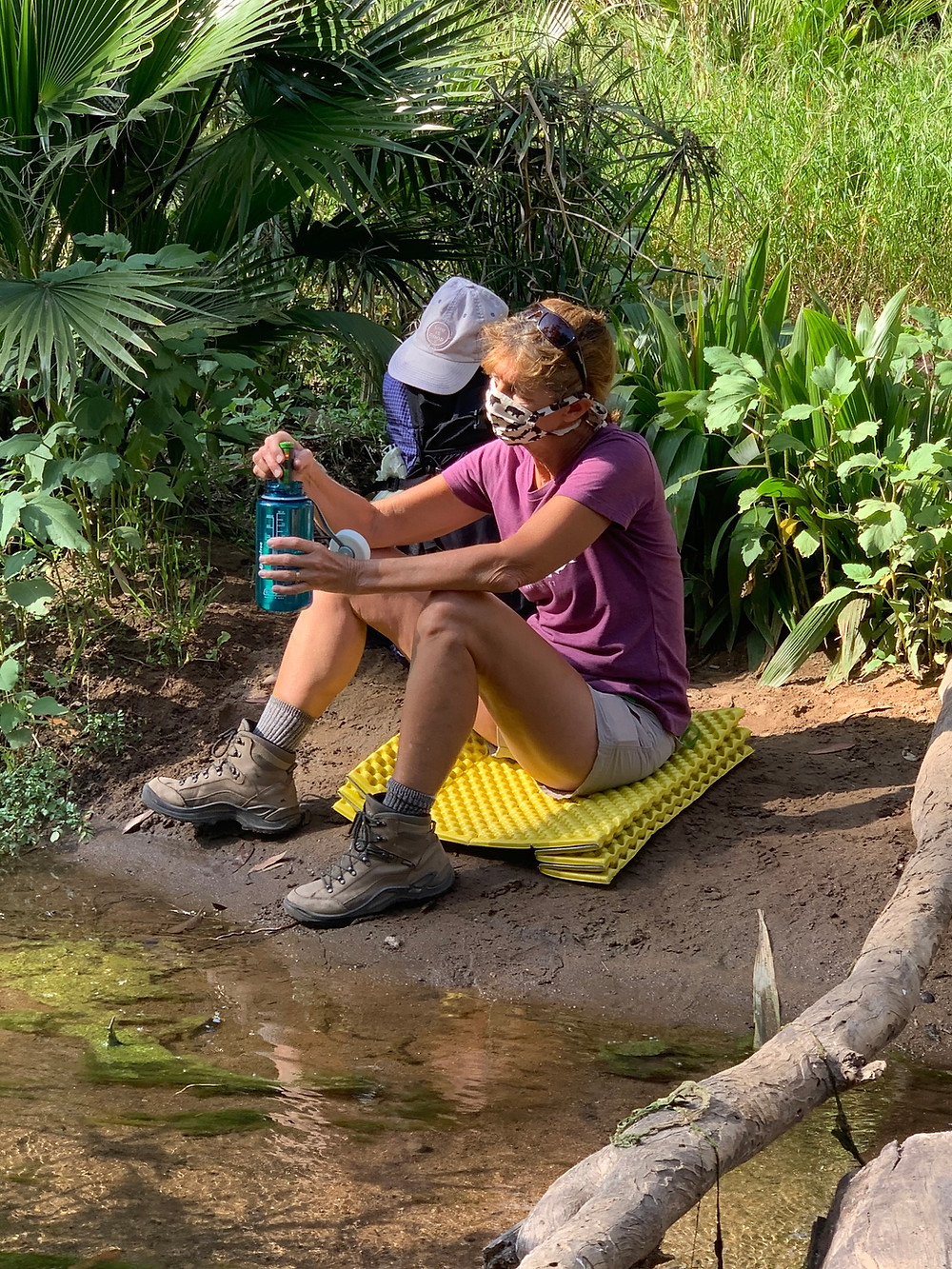 Backpacker Filtering Water with Face Mask