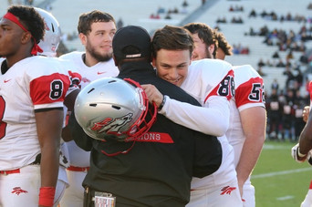 Former South Pointe wide receiver, Bo Taylor, a college baseball commit, embraces Coach Melvin Simpkins just after scoring the final touchdown of the state championship game.