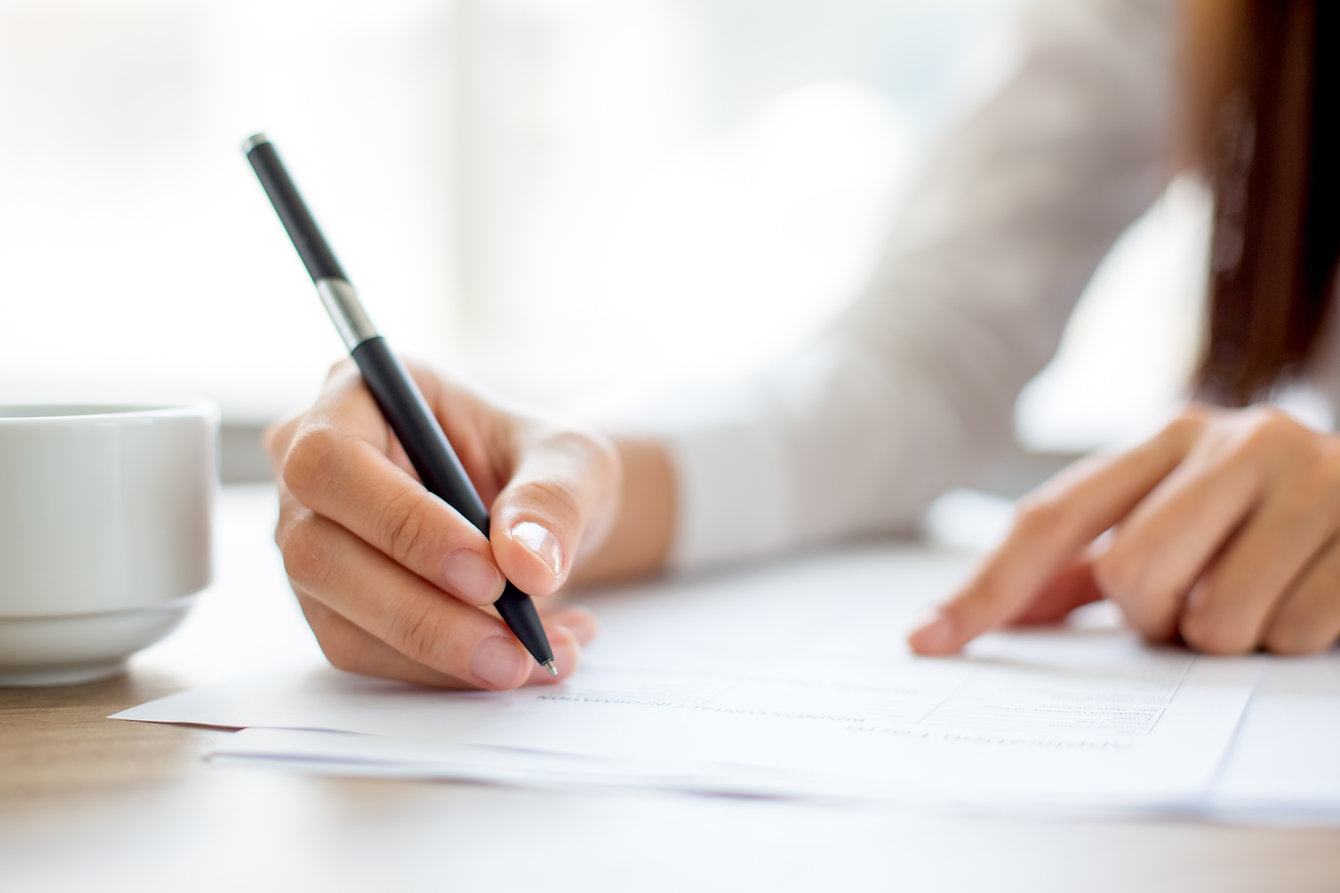Hand of businesswoman writing on paper i