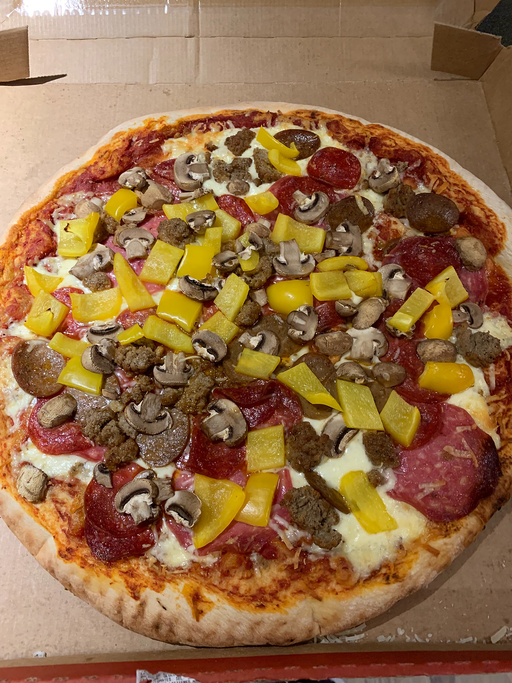 Costco Kirkland Signature Four Meat Pizza with additional toppings