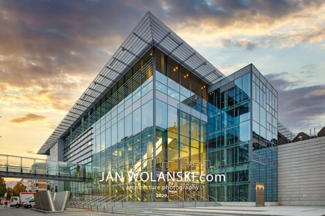 Архитектурная фотография стеклянного фасада современного здания на заходе солнца. Архитектурный фотограф Ян Волянский.