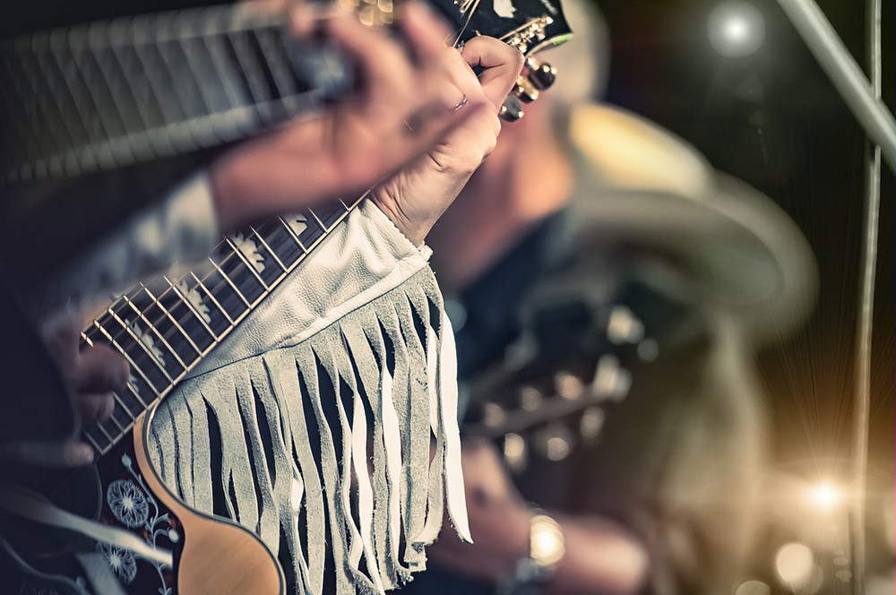 Close-up hands playing guitar wearing fringed jacket and country hat in background.
