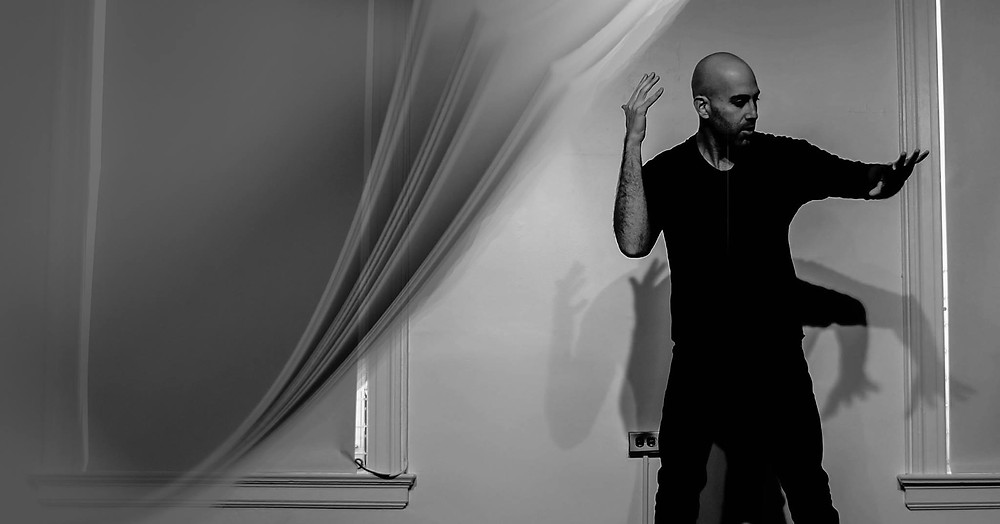 [Image Description: Black and white composite image, a detail of pages flipping open onto a photograph of tall white man, Douglas Ridloff, wearing a black t-shirt and dark jeans, using ASL with arms outspread. Multiple shadows of his arms are on the wall behind him.]