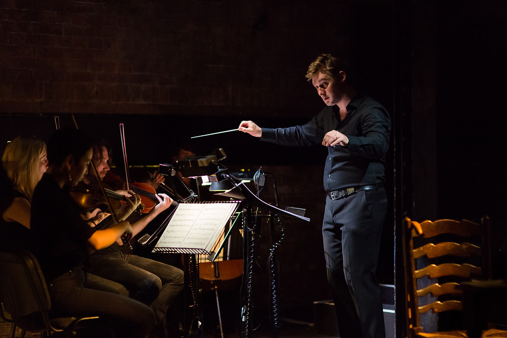 Jonathan Hargreaves stands with arms wide, holding a white conductor's baton in his right hand. The front row of musicians are playing: two violinists, a viola player and cellist