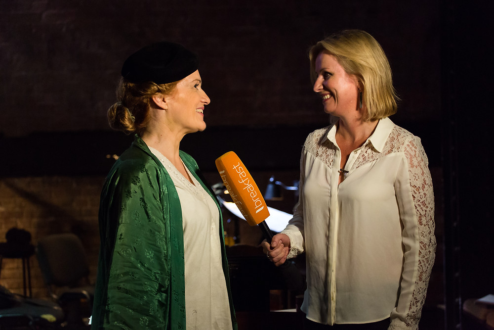 Joanne is in costume on the left: black beret, green silk kimono robe over a white nightdress. Emma Keeling is on the right, pointing a large orange microphone towards Joanne. Both women have broad smiles.