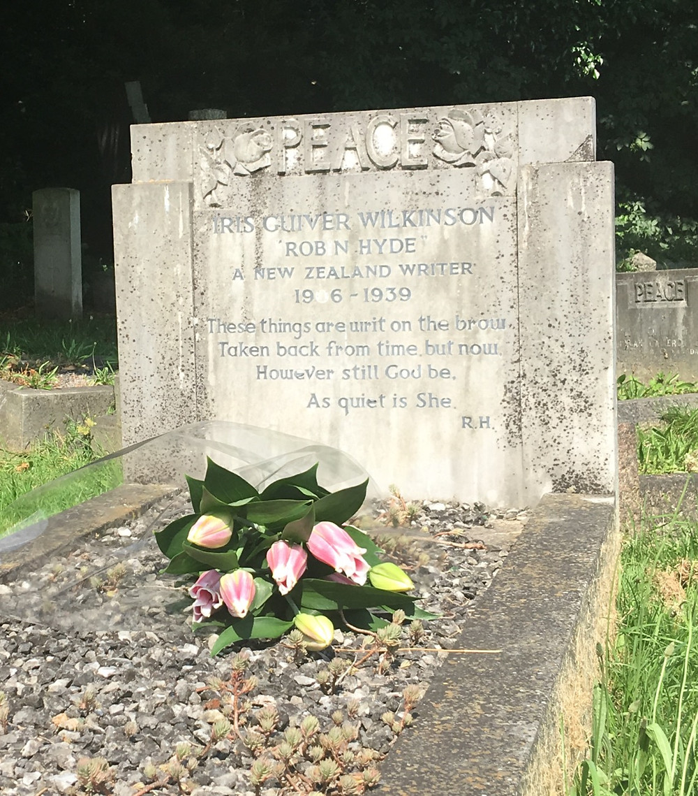 A bunch of pink lilies lain across a pebble-filled grave with a pale tombstone at the head. The inscription is reproduced to the left of the image.