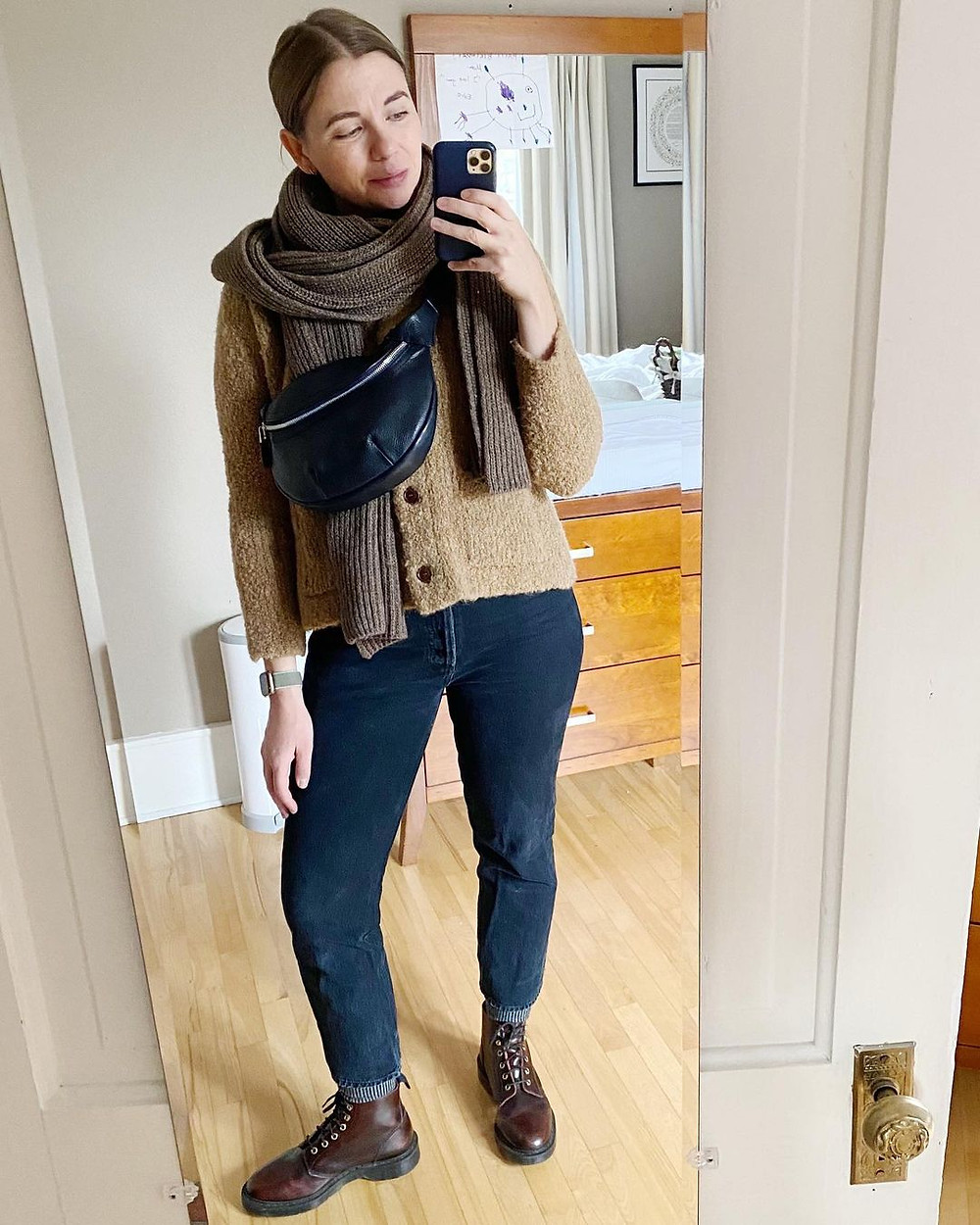 woman wears black fanny pack, brown scarf, light brown fuzzy sweater, blue jeans, and brown boots while posing for a selfie in a full length mirror indoors