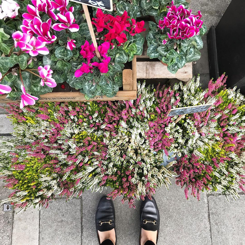 woman wears jordaan bit black leather loafer while standing next to crates of assorted brightly colored flowers